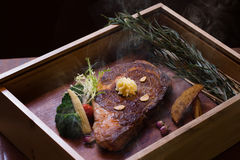 Roast smoked Angus eye steak on wooden box in black background Royalty Free Stock Photos