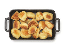 Roast spuds. Isolated Roast Potato's in roasting dish Stock Images
