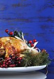 Roast Turkey on dark blue rustic wood background - vertical with copyspace. Scrumptious roast turkey chicken on platter with festive decorations for stock photos