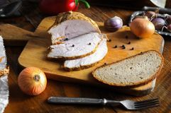 Roast turkey meat with bay leaf, pepper and garlic on old cutting board, Vintage country table. Delicious roast turkey meat with bay leaf, pepper and garlic on stock images