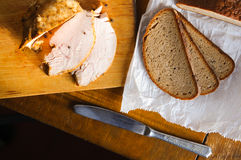 Roast turkey meat with bread sclices on old cutting board, Vintage country table. Delicious roast turkey meat with with bread sclices on old cutting board stock photo