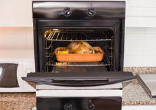 Roast turkey in oven for christmas dinner. At home in the kitchen royalty free stock photo