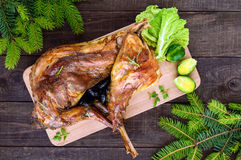 Roast whole rabbit stuffed with prunes on a wooden board with baked carrots stock image