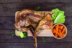 Roast whole rabbit on a wooden board with baked carrots and Brussels sprouts on a dark background. A festive meal. The top view Royalty Free Stock Photos