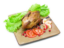 Roast wild duck carcass on white background. Roast wild duck carcass with lettuce, tomatoes, apples and cranberries on a plate on white fone.gorizontalnoe photo stock images