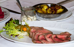 Roastbeef in a restaurant with potatoes. An dressing Royalty Free Stock Photography