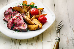 Roastbeefsteak mit Kartoffelkeilen und -tomate Lizenzfreie Stockfotos