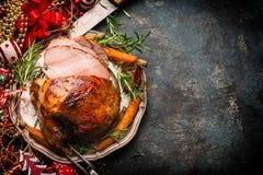 Roasted切了在板材的圣诞节火腿有叉子、刀子和欢乐装饰的在黑暗的土气背景 免版税库存图片