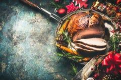 Roasted切了在欢乐桌背景的圣诞节火腿与装饰 免版税库存照片