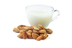 Roasted Almond nut in shell and a cup of almonds milk on white background Royalty Free Stock Photo