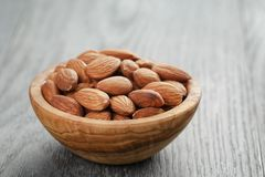 Roasted almonds in bowl on gray wooden table Royalty Free Stock Photography
