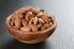 Roasted almonds in bowl on slate background Royalty Free Stock Image