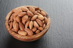 Roasted almonds in bowl on slate background Stock Photos