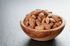 Roasted almonds in bowl on slate background Stock Photo