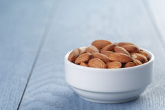 Roasted almonds in white bowl on wooden table Royalty Free Stock Images