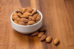 Roasted almonds in white porcelain bowl Stock Photos