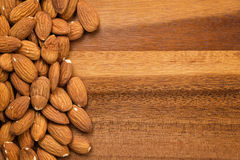 Roasted almonds on wooden table Stock Images