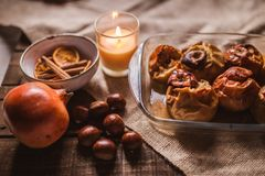 Roasted apples in a glass tray with chestnuts, candle, cinnamon, orange and pomegranate stock photos
