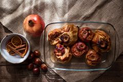Roasted apples in a glass tray with chestnuts, cinnamon, orange and pomegranate royalty free stock photos