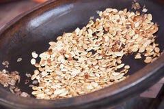 Roasted argan kernels in a frying pan. Stock Image
