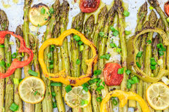 Roasted asparagus spears with lemon slices, cherry tomatoes, bell pepper rings Stock Image