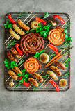 Roasted assorted sausages on an oven grill stock image