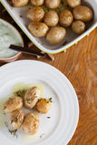 Roasted baby potatoes with thyme. Olive oil and salt with tzatziki Stock Images