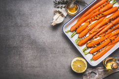 Roasted Baby Topped carrots on baking sheet with thyme, honey, garlic and lemon on gray concrete background, top view, border. Stock Photo