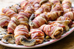 Roasted bacon wraps with white mushrooms. Mediterranean cuisine - baked bacon slices wrapped around chicken white meat arranged with white (button) mushrooms Stock Photos