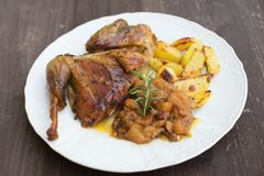 Roasted or baked Guinea fowl served with baked potatoes and sweet onion with apples and raisins. Stock Image