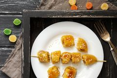 A roasted banana on a skewer is sprinkled with sesame seeds, on a black wooden tray. Multicolored candied fruits. View from above Royalty Free Stock Image