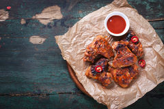 Roasted barbecue chicken wings with bbq sauce, italian herbs, olive oil and pepper. Top view with copy space stock photography