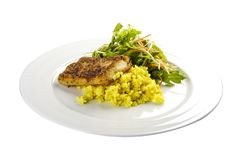 Roasted bass with creamy rice. On a white background stock image