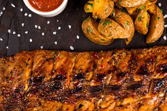 Roasted bbq ribs with fry potatoes and souce Royalty Free Stock Photos
