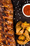 Roasted bbq ribs with fry potatoes and souce Stock Photography