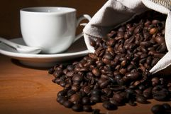 Roasted beans of coffee and a cup on the background Royalty Free Stock Photography