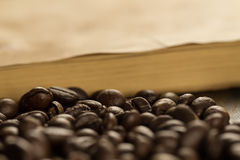 Roasted beans on old vintage open book. Menu, recipe, mock up. Wooden background. Royalty Free Stock Image