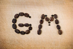 Roasted beans are set in shape of good morning combination. Letters formed by coffee seeds on wooden background. Close up. Royalty Free Stock Image