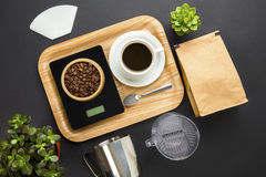 Roasted Beans On Weight Scale With Coffee Cup In Tray. Overhead view of roasted beans on digital weight scale with coffee cup in tray on gray background royalty free stock photo