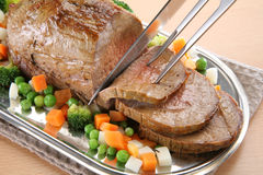 Roasted Beef. On tray, cutted, with fresh vegetables Royalty Free Stock Photos