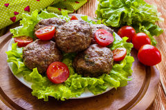 Roasted beef cutlets, green salad and small tomatoes on white plate Royalty Free Stock Photos