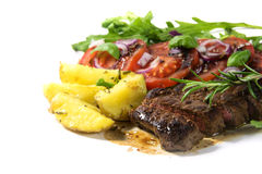Roasted beef filet mignon with potatoes and tomato arugula salad. Isolated on a white background, close up with selected focus and narrow depth of field stock image
