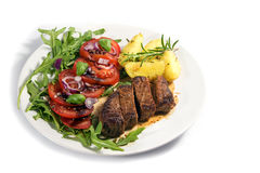 Roasted beef filet mignon with potatoes and tomato arugula salad Stock Photography