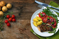 Roasted beef filet mignon with potatoes and tomato arugula salad. On a rustic wooden board with copy space, view from above royalty free stock image