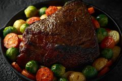 Roasted beef with honey glazed vegetables, served in cast iron vintage pan. festive dinner stock photos
