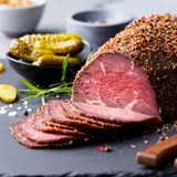 Roasted beef, pastrami on slate cutting board. Close up.  stock photos