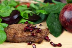 Roasted beef steak served with fresh herbs, vegetables and pomeg. Roasted beef steak served with fresh herbs, beetroot and fresh peeled pomegranate on a wooden Royalty Free Stock Photography