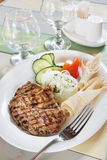 Roasted beef steak with sliced tomato and cucumbers on the served table Stock Photography