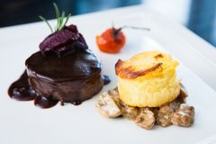 Roasted beef tenderloin. With herb-potato muffin, mushroom ragout, baked tomatoes and rosemary-currant sauce royalty free stock images