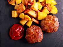 Roasted beefsteaks and potatoes with carrot Royalty Free Stock Photo